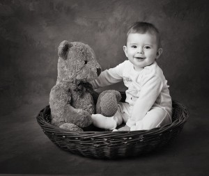 Baby in a basket with teddy