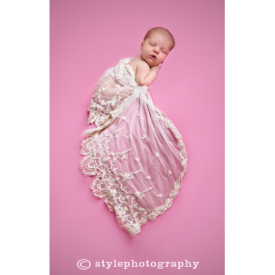 A newborn baby girl with pink background