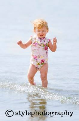 A toddler paddles in the sea