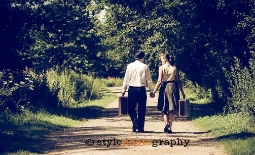 A couple walk hand-in-hand along a country lane with their suitcases