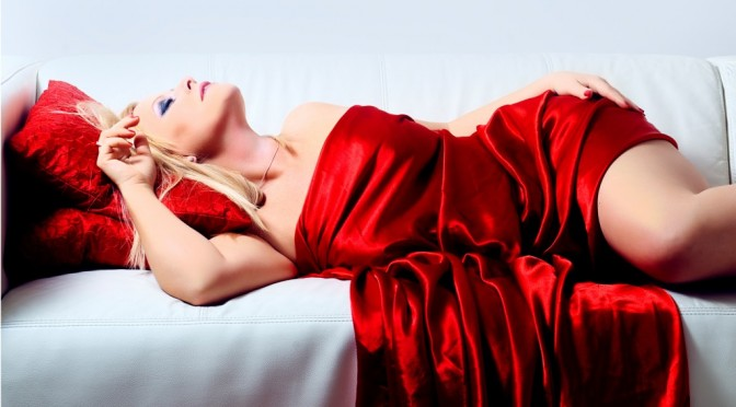 A woman posing on a bed draped in a red satin sheet