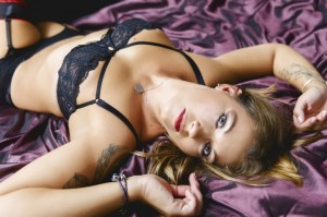A boudoir shot of a woman posing on a bed