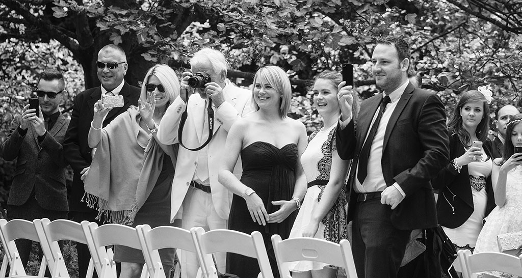 Guests with cameras and phones at a wedding